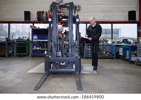 Mechanic going over the quality control checklist after a full revision and uphaul of a used forklift - stock photo