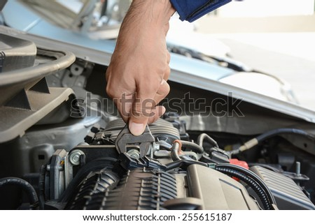 Mechanic hand holding wrench fixing car engine