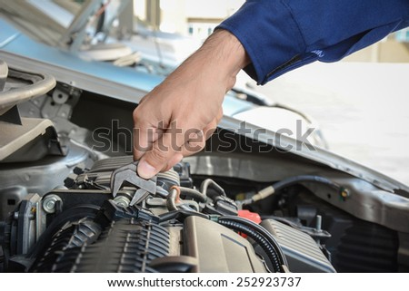 Mechanic hand with wrench fixing car engine