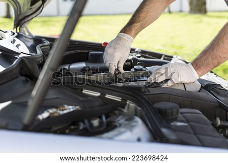 Mechanic hands installing new spark plugs in a car - stock photo