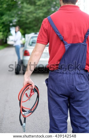 Mechanic helping young woman after unexpected vehicle breakdown - stock photo