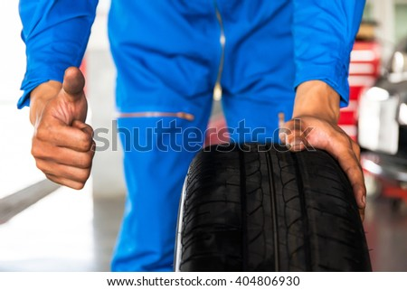 Mechanic holding a car wheel with thumb up sign in car garage service  - stock photo