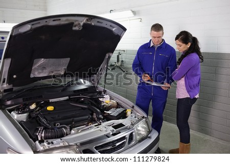 Mechanic holding a clipboard next to a woman in a garage - stock photo