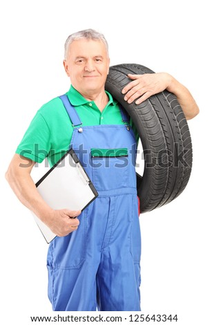 Mechanic holding a vehicle tire and a clipboard isolated on white background