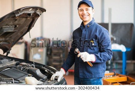 Mechanic holding a wrench while fixing a car in his shop - stock photo