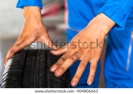 Mechanic holding and checking car wheel in car garage service.