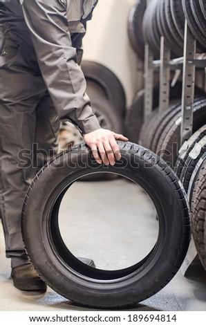 Mechanic holding car tire at warehouse. - stock photo