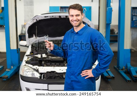 Mechanic holding pair of wrenches at the repair garage - stock photo