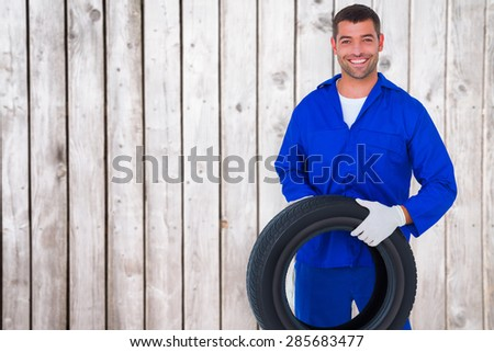 Mechanic holding tire on white background against digitally generated grey wooden planks