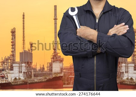 mechanic holding tool for repair at petrochemical oil refinery in sunrise - stock photo