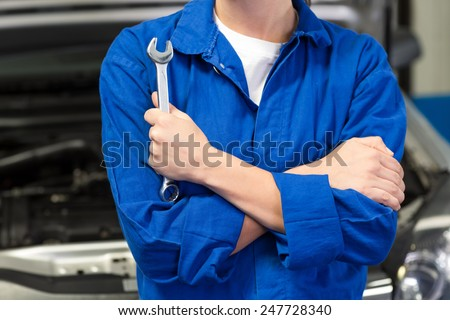 Mechanic holding wrench with crossed arms at the repair garage - stock photo