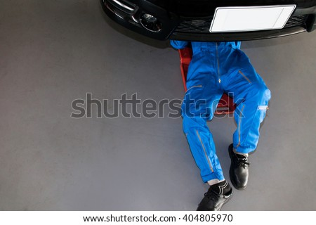Mechanic in blue uniform lying down and working under car at the garage.