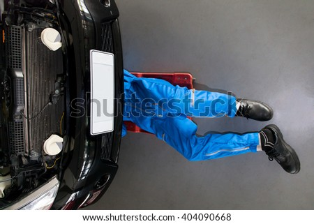 Mechanic in blue uniform lying down and working under car at the repair garage - stock photo