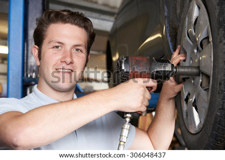 Mechanic In Garage Using Air Hammer On Car Wheel