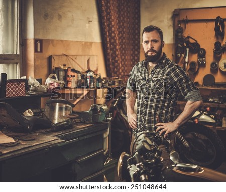 Mechanic in motorcycle custom garage - stock photo