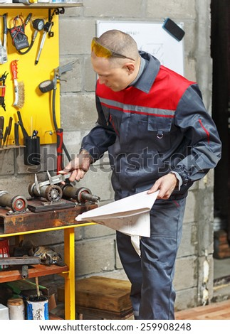 Mechanic in workplace. Man with  plan measures  detail