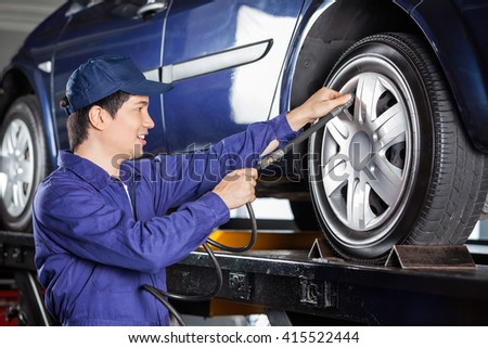Mechanic Inflating Car Tire - stock photo