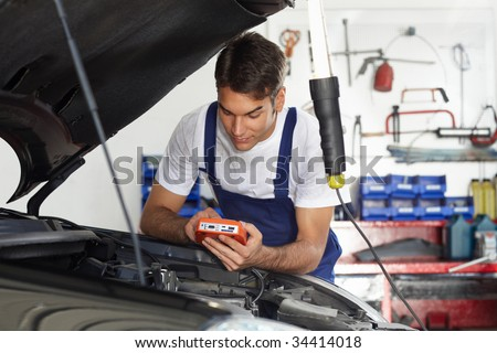 mechanic leaning on bonnet with tester equipment - stock photo