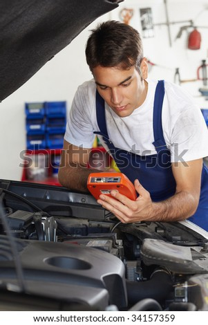 mechanic leaning on bonnet with tester equipment and looking at camera - stock photo