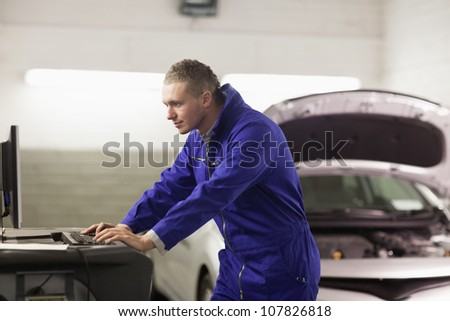 Mechanic looking at a computer in a garage
