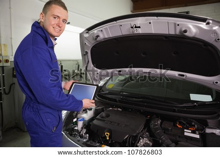 Mechanic looking at camera while holding a tablet computer in a garage