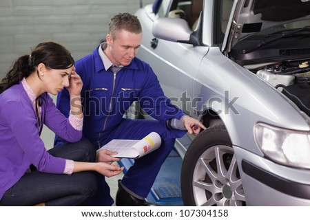 Mechanic looking at the car wheel next to a client in a garage