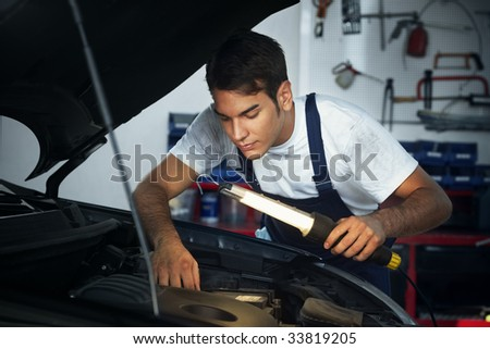 mechanic looking to car engine and holding lamp - stock photo