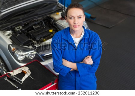 Mechanic looking up at camera at the repair garage - stock photo