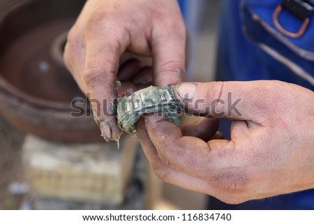 Mechanic lubricate a roller bearing with lithium grease - stock photo