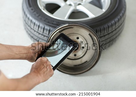 Mechanic man hands working taken a photo to a tire with a tablet - stock photo