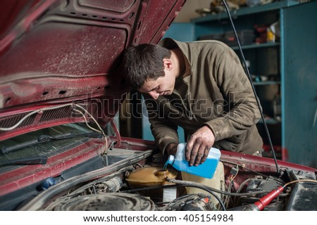 Mechanic man worker pouring antifreeze from small bottle in the cooling system during car repair works in auto service center - stock photo
