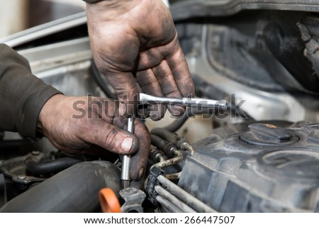 mechanic man worker with socket wrench during car repair works in auto service center