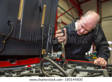 Mechanic measuring the acidity of the batteries in a forklift. - stock photo