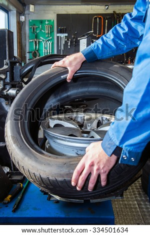 Mechanic mounting a tire on a light weight alloy rim in a garage - stock photo