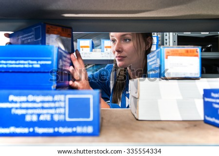Mechanic picking up spare parts in boxes from a storage rack in a supply room - stock photo