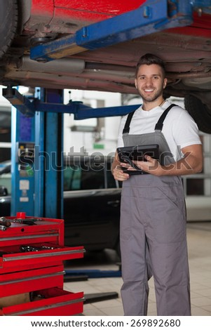 Mechanic Posing Under the Car with a Digital Tablet