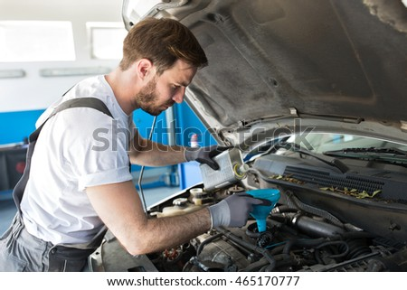 Mechanic poured new oil in a car
