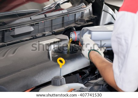 Mechanic pouring car's oil in a car service garage - stock photo