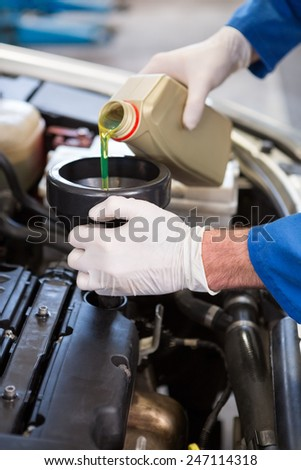 Mechanic pouring oil into car at the repair garage - stock photo
