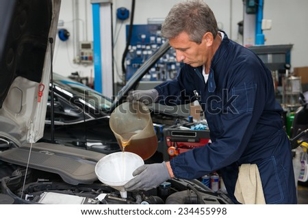 Mechanic Pouring Oil Into Car Engine At Workshop - stock photo
