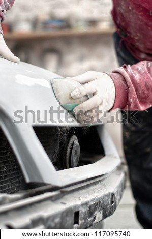 Mechanic preparing the body of a car for a paint job by applying the first layer of polish - stock photo