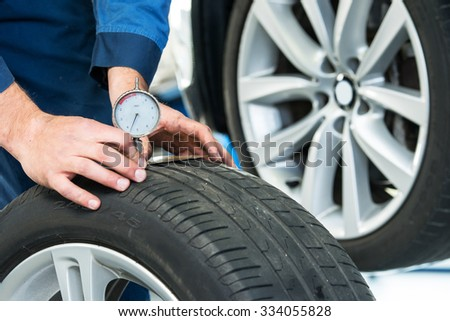 Mechanic, pressing a gauge into a tire tread to measure its depth for vehicle and road safety - stock photo