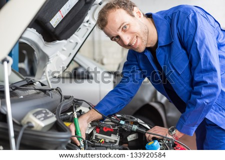 Mechanic repairing the motor or electric parts of a car in a garage - stock photo