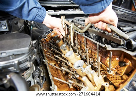 mechanic repairman at automobile car engine maintenance repair work - stock photo