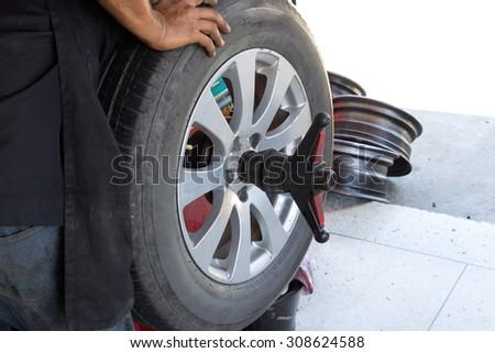 Mechanic repairman balancing automobile car wheel on balancer - stock photo