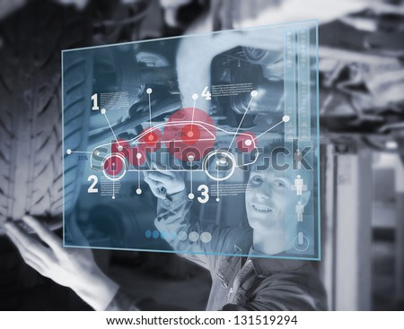 Mechanic reparing car while looking at futuristic interface with diagram - stock photo