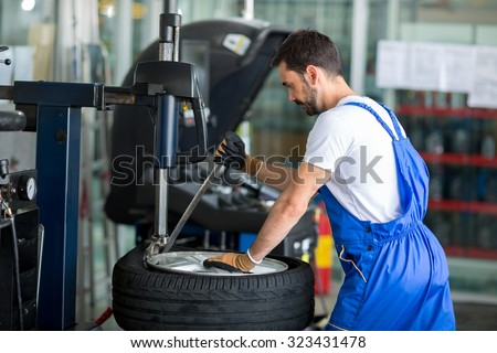 mechanic replace tires on wheels in a workshop - stock photo