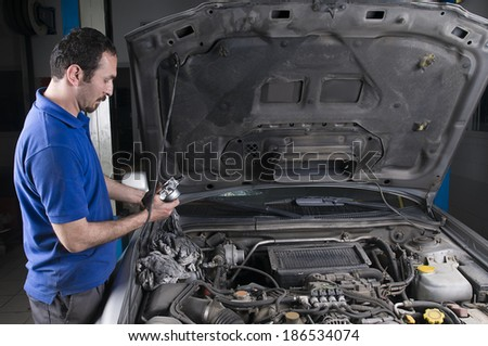 Mechanic Replacing Broken Part of an Auto    - stock photo