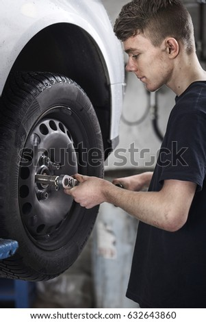 Mechanic´s apprentice changing tires on a car.