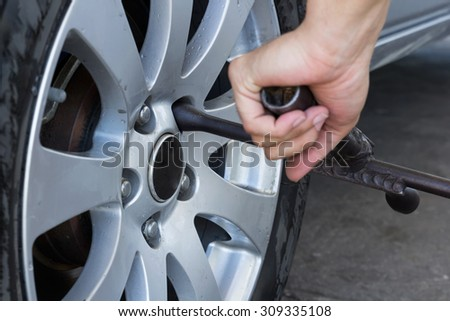 Mechanic screwing or unscrewing changing car wheel by wrench  - stock photo